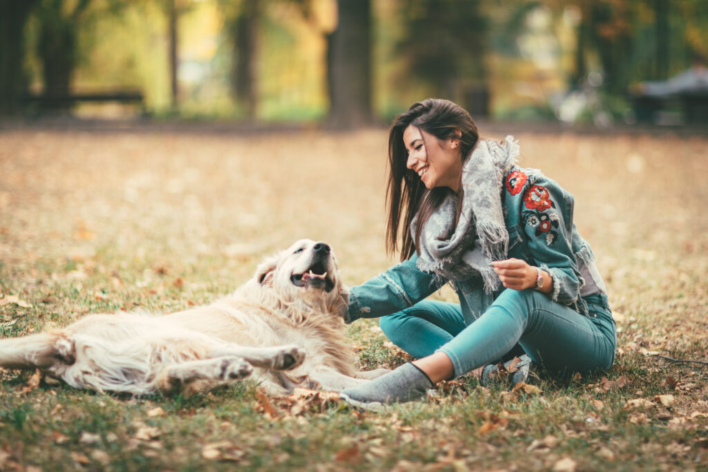 Cute young woman enjoying in city park in autumn colors. She is sitting on the ground covered with leaves and having fun with her dog.